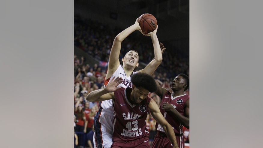 Gonzaga's Kyle Wiltjer, back, grabs a rebound against Saint Joseph's DeAndre Bembry (43) during the first half of an NCAA college basketball game in Spokane, Wash., Wednesday, Nov. 19, 2014. (AP Photo/Young Kwak)