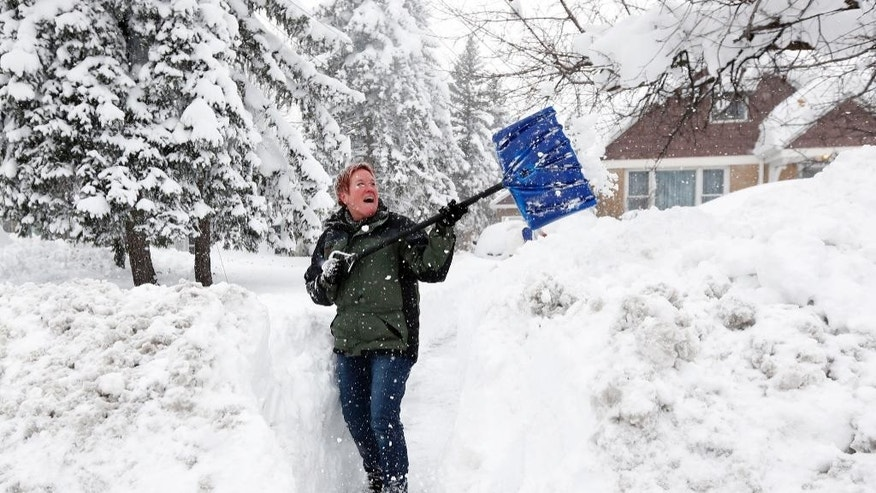 Sue Radka helps shovel out a friends driveway on Wednesday, Nov. 19, 2014, in Lancaster, N.Y. Lake-effect snow pummeled areas around Buffalo for a second straight day, leaving residents stuck in their homes as officials tried to clear massive snow mounds with another storm looming. (AP Photo/Mike Groll)