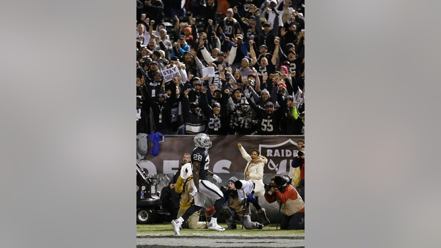 Fans cheer as Oakland Raiders running back Latavius Murray (28) scores on an 11-yard touchdown run against the Kansas City Chiefs during the first quarter of an NFL football game in Oakland, Calif., Thursday, Nov. 20, 2014. (AP Photo/Ben Margot)