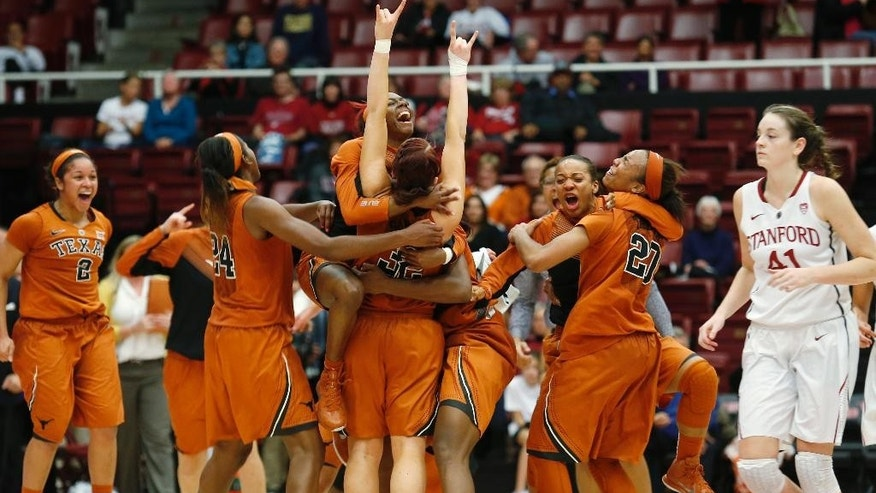 Texas players embrace after defeating Stanford 87-81 in overtime in an NCAA college basketball game in Stanford, Calif., Thursday, Nov. 20, 2014. (AP Photo/Beck Diefenbach)