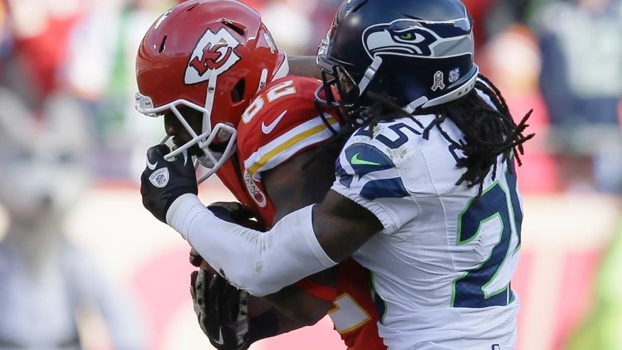 Seattle Seahawks cornerback Richard Sherman (25) grabs the face mask of Kansas City Chiefs wide receiver Dwayne Bowe (82) in the second half of an NFL football game in Kansas City, Mo., Sunday, Nov. 16, 2014. (AP Photo/Charlie Neibergall)