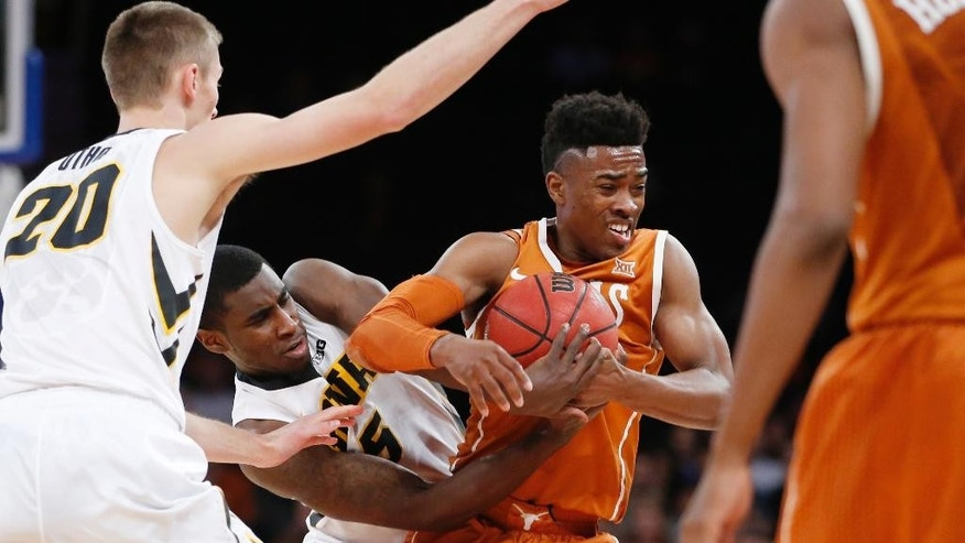 Iowa guard Anthony Clemmons (5) tries to strip the ball from Texas guard Isaiah Taylor (1) in the first half of an NCAA basketball game at Madison Square Garden in New York, Thursday, Nov. 20, 2014.  (AP Photo/Kathy Willens)