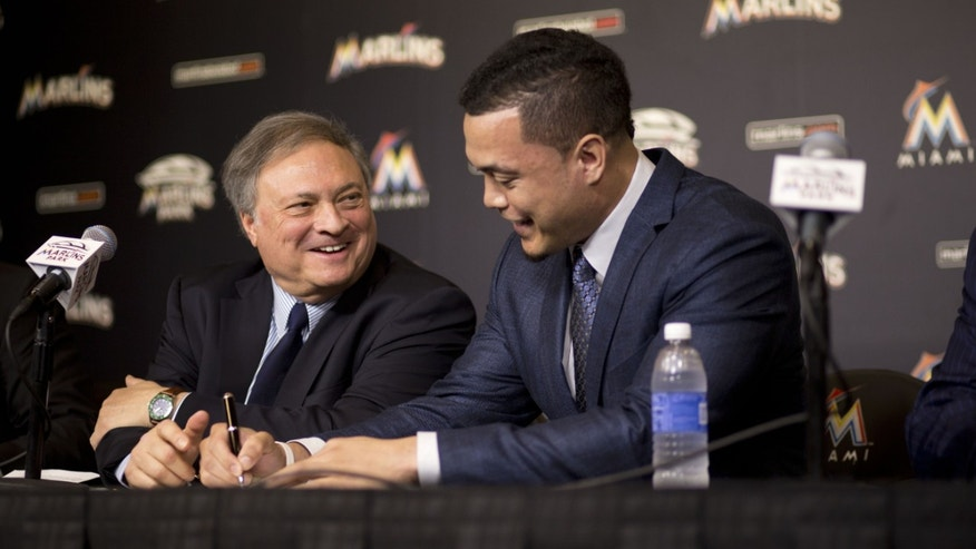 Miami Marlins baseball team owner Jeffrey Loria, left, smiles as he watches Giancarlo Stanton sign his record $325 million, 13-year contract at a news conference Wednesday, Nov. 19, 2014, in Miami. The contract is the most lucrative for an American athlete and the longest in baseball history. (AP Photo/J Pat Carter)