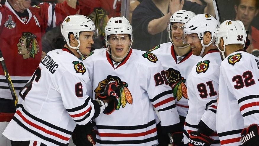 Chicago Blackhawks' Patrick Kane, second form left, celebrates his goal with his teammates during the third period of an NHL hockey game against the Calgary Flames in Calgary, Alberta, Thursday, Nov. 20, 2014. (AP Photo/The Canadian Press, Jeff McIntosh)