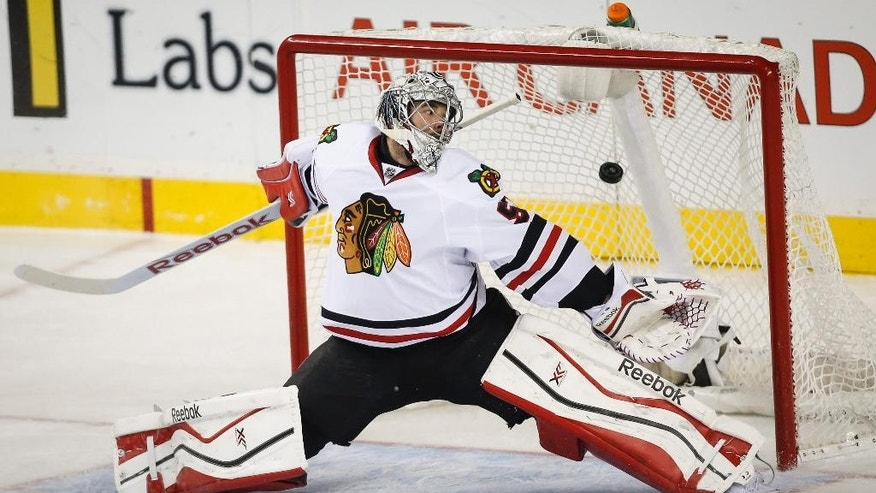 Chicago Blackhawks goalie Corey Crawford lets in a goal during the second period of an NHL hockey game, Thursday, Nov. 20, 2014 in Calgary, Alberta. (AP Photo/Canadian Press, Jeff McIntosh)