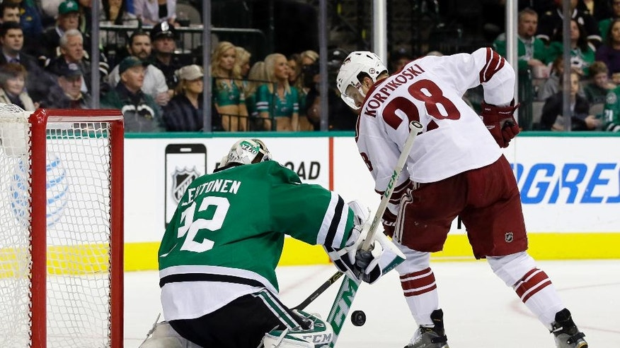 Dallas Stars goalie Kari Lehtonen (32), of Finland, deflects a shot from Arizona Coyotes' Lauri Korpikoski (28), also of Finland, in the second period of an NHL hockey game, Thursday, Nov. 20, 2014, in Dallas. (AP Photo/Tony Gutierrez)