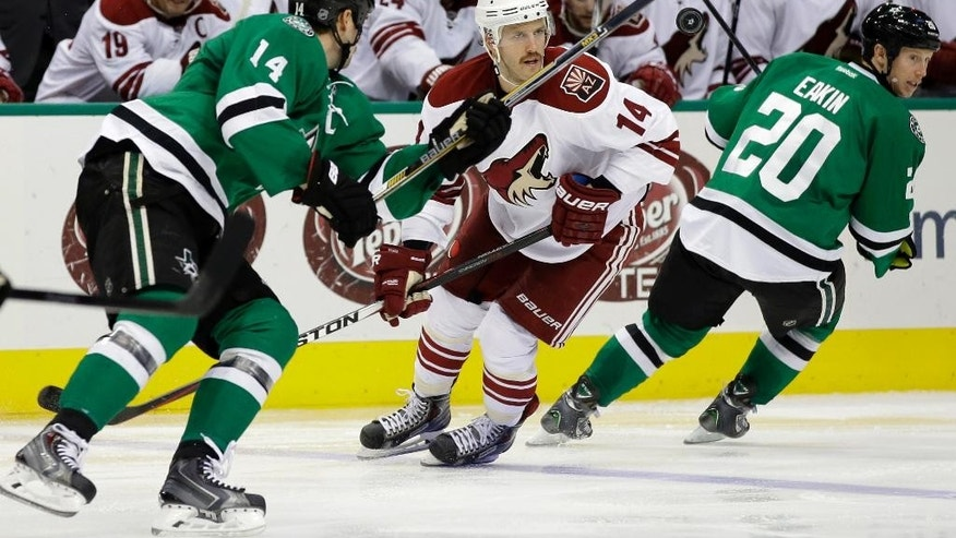 Dallas Stars' Jamie Benn (14) and Arizona Coyotes' Joe Vitale (14) watch an airborne puck in the second period of an NHL hockey game, Thursday, Nov. 20, 2014, in Dallas. Stars' Cody Eakin (20) also watches. (AP Photo/Tony Gutierrez)
