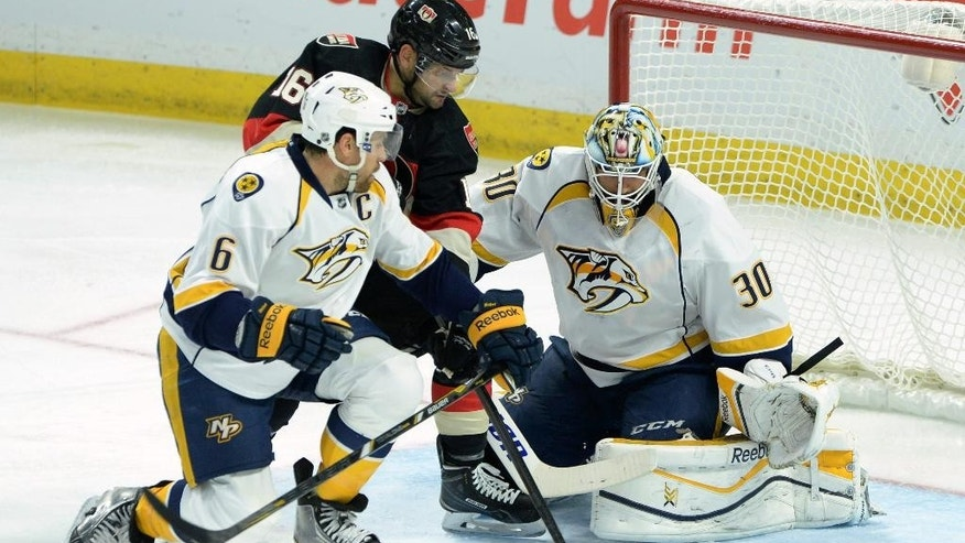 Ottawa Senators' Clarke MacArthur, middle, fights for the puck against Nashville Predators' Shea Weber, left, and Carter Hutton during NHL hockey action in Ottawa on Thursday, Nov. 20, 2014. (AP Photo/The Canadian Press, Sean Kilpatrick)