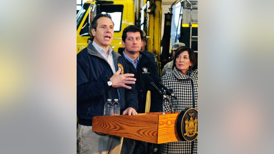 Governor Andrew M. Cuomo, left, speaks with the media as Erie County Executive Mark Poloncarcz, center, and Lt. Gov.Kathy Hochul, right, listen during a storm briefing at the Thruway Authority in Cheektowaga, N.Y. Wednesday, Nov.19, 2014. The Buffalo area found itself buried under as much as 5½ feet of snow Wednesday, with another lake-effect storm expected to bring 2 to 3 more feet by late Thursday. (AP Photo/Gary Wiepert)