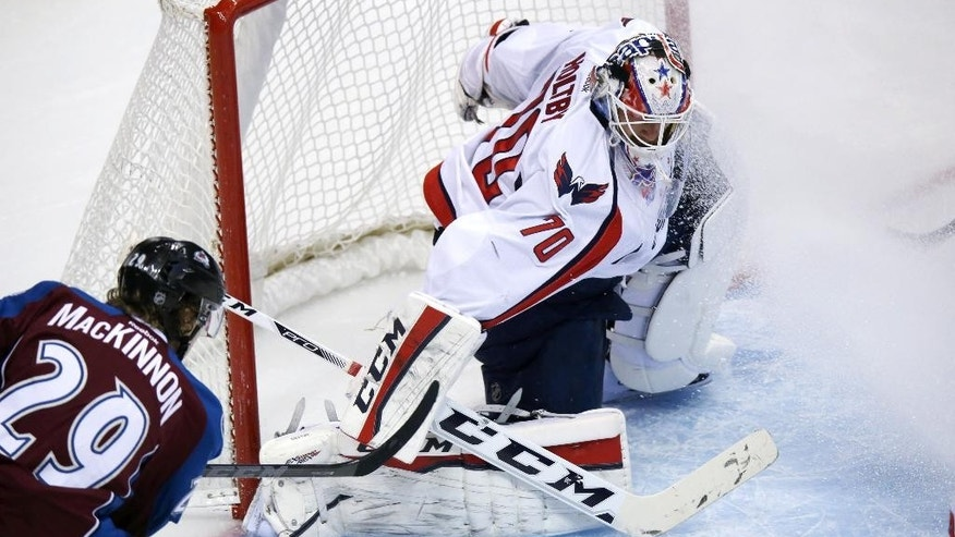 Washington Capitals goalie Braden Holtby, back, makes stop of shot off the stick of Colorado Avalanche center Nathan MacKinnon in the first period of an NHL hockey game in Denver on Thursday, Nov. 20, 2014. (AP Photo/David Zalubowski)
