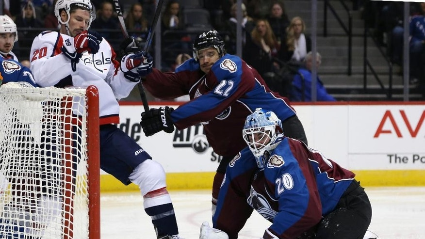 Colorado Avalanche goalie Reto Berra, front, of the Czech Republic, tries to cover puck as Washington Capitals right wing Troy Brouwer, back left, is cleared from side of net by Avalanche defenseman Zach Redmond in the second period of an NHL hockey game in Denver on Thursday, Nov. 20, 2014. (AP Photo/David Zalubowski)