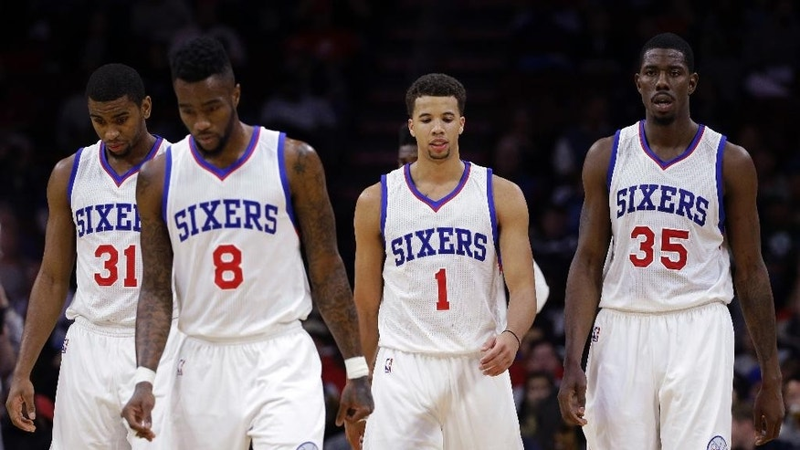 Philadelphia 76ers' Hollis Thompson (31), Tony Wroten (8), Michael Carter-Williams (1) and Henry Sims (35) walk onto the court after a timeout during the second half of an NBA basketball game against the Boston Celtics, Wednesday, Nov. 19, 2014, in Philadelphia. Philadelphia lost their 11th straight game to start the season to Boston, 90-101. (AP Photo/Matt Slocum)