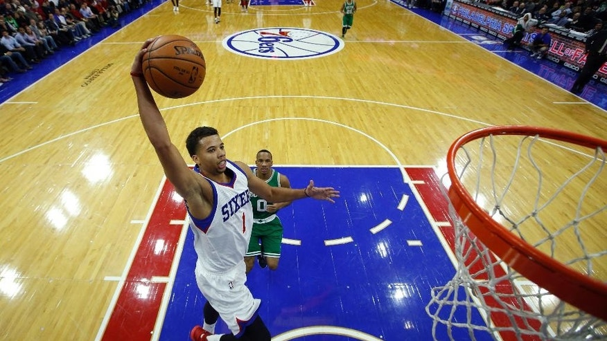 Philadelphia 76ers' Michael Carter-Williams (1) goes up for a dunk past Boston Celtics' Avery Bradley (0) during the first half of an NBA basketball game, Wednesday, Nov. 19, 2014, in Philadelphia. (AP Photo/Matt Slocum)
