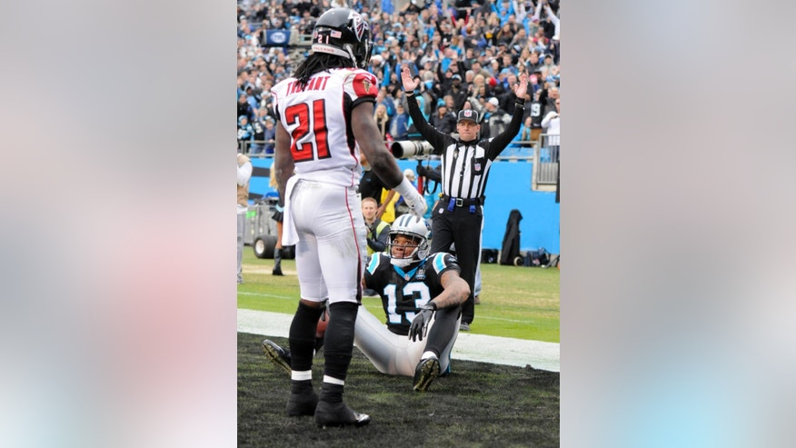 Carolina Panthers' Kelvin Benjamin (13) grins at Atlanta Falcons' Desmond Trufant (21) after catching a touchdown pass in the second half of an NFL football game in Charlotte, N.C., Sunday, Nov. 16, 2014. (AP Photo/Mike McCarn)