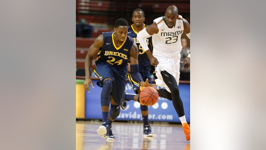 Drexel's Rodney Williams pushes the ball up court against Miami's Tonye Jekiri, right, during the first half of an NCAA college basketball game at Charleston Classic in Charleston, S.C., Thursday, Nov. 20, 2014. Drexel's Mohamed Bah trails the play. (AP Photo/Mic Smith)