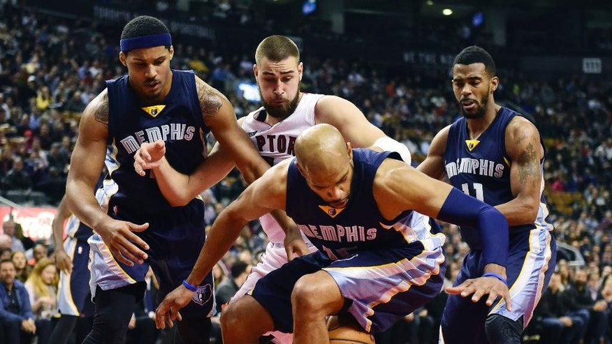 Toronto Raptors' Jonas Valanciunas, second from back left, battles for a loose ball with, from left to right, Memphis Grizzlies' Jarnell Stokes, Vince Carter and Mike Conley during first-half NBA basketball action in Toronto, Wednesday, Nov. 19, 2014. (AP Photo/The Canadian Press, Frank Gunn)