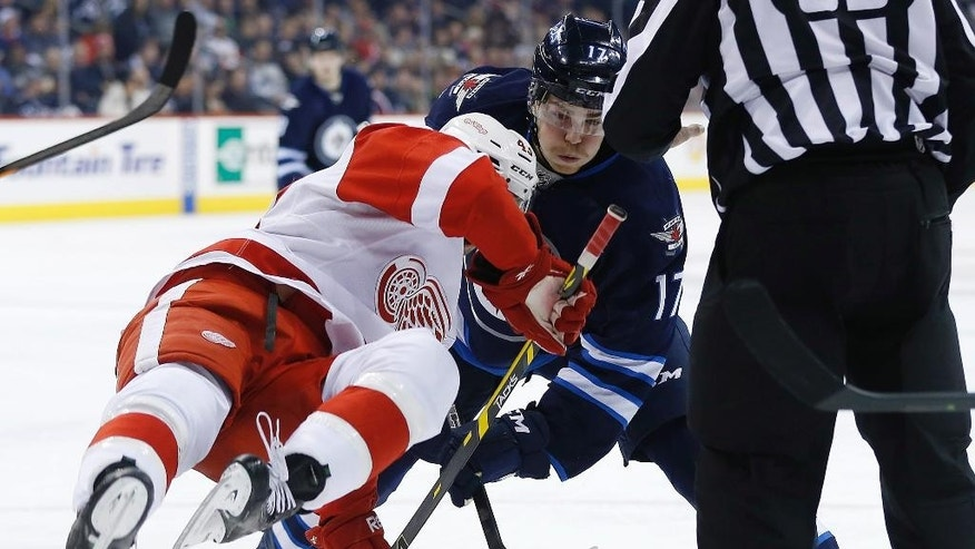 Winnipeg Jets' Adam Lowry (17) upends Detroit Red Wings' Darren Helm (43) during the second period of an NHL hockey game, Thursday, Nov. 20, 2014 in Winnipeg, Manitoba. (AP Photo/Canadian Press, John Woods)