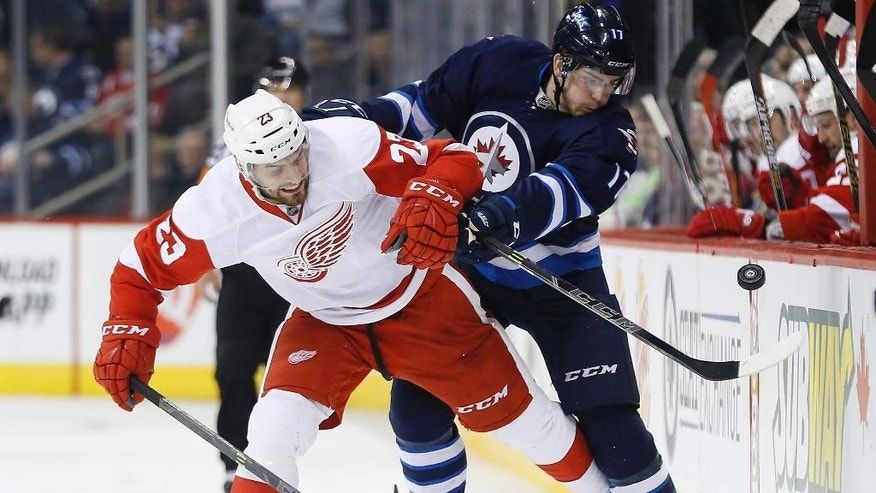 Detroit Red Wings' Brian Lashoff (23) and Winnipeg Jets' Adam Lowry (17) go for the puck along the boards  during the second period of an NHL hockey game, Thursday, Nov. 20, 2014 in Winnipeg, Manitoba. (AP Photo/Canadian Press, John Woods)