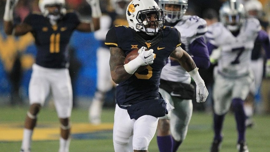 West Virginia's Mario Alford (5) carries the ball after a catch for a touchdown during the fourth quarter of an NCAA college football game against Kansas State in Morgantown, W.Va., on Thursday, Nov. 20, 2014. Kansas State won 26-20. (AP Photo/Chris Jackson)