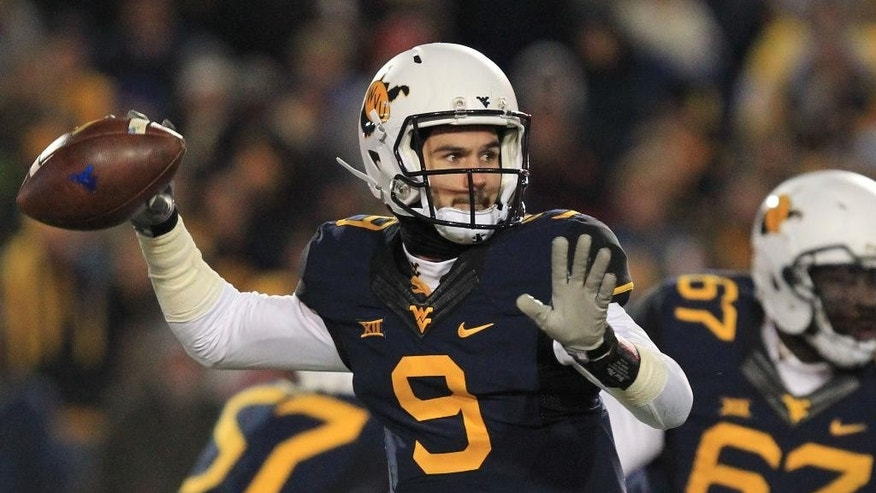 West Virginia quarterback Clint Trickett (9) attempts a pass during the first half of an NCAA college football game against Kansas State in Morgantown, W.Va., on Thursday, Nov. 20, 2014. (AP Photo/Chris Jackson)