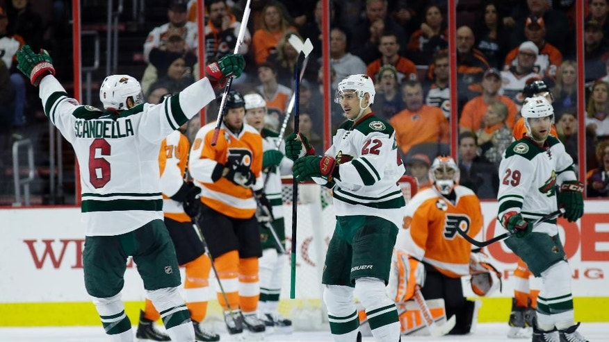 Minnesota Wild's Marco Scandella (6) and Nino Niederreiter (22), of the Czech Republic, celebrate after Niederreiter's goal during the second period of an NHL hockey game against the Philadelphia Flyers, Thursday, Nov. 20, 2014, in Philadelphia. (AP Photo/Matt Slocum)