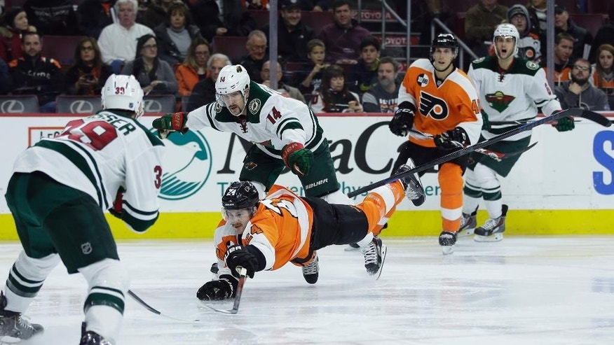 Philadelphia Flyers' Matt Read (24) battles for the puck against Minnesota Wild's Justin Fontaine (14) and Nate Prosser (39) during the second period of an NHL hockey game, Thursday, Nov. 20, 2014, in Philadelphia. (AP Photo/Matt Slocum)