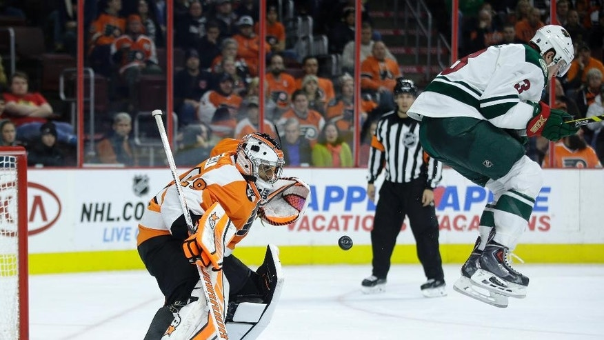 Philadelphia Flyers' Ray Emery, left, blocks a shot as Minnesota Wild's Charlie Coyle leaps out of the way during the third period of an NHL hockey game, Thursday, Nov. 20, 2014, in Philadelphia. Minnesota won 3-2. (AP Photo/Matt Slocum)