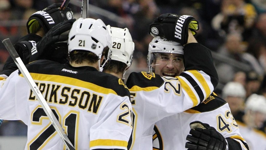 Boston Bruins' Matt Bartkowski, right, celebrates a goal with teammates against the Columbus Blue Jackets' during the third period of an NHL hockey game Friday, Nov. 21, 2014, in Columbus, Ohio. The Bruins defeated the Blue Jackets 4-3 in a shootout. (AP Photo/Jay LaPrete)