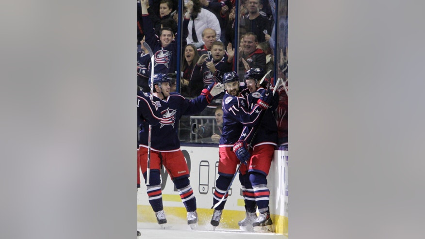 From left to right, Columbus Blue Jackets' Boone Jenner Nick Foligno and Ryan Johansen celebrate their goal against the Boston Bruins during the first period of an NHL hockey game Friday, Nov. 21, 2014, in Columbus, Ohio. (AP Photo/Jay LaPrete)