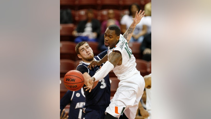Miami's Sheldon McClellan, right, passes the ball against Akron's Pat Forsythe during the first half of an NCAA college basketball game at the Charleston Classic tournament in Charleston, S.C., Friday, Nov. 21, 2014. (AP Photo/Mic Smith)
