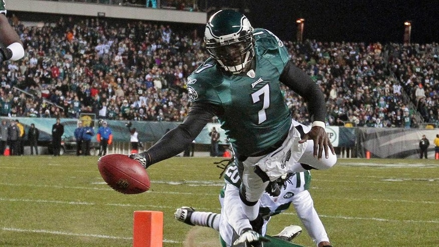 FILE - In this Dec. 18, 2011, file photo, Philadelphia Eagles quarterback Michael Vick (7) scores a touchdown as New York Jets defensive back Kyle Wilson can't make the stop in the first half of an NFL football game in Philadelphia. In the 13 years since his arrival as the fastest man on the field who also happened to have the best arm, Vick's impact has been felt in the way quarterbacks and offenses evolve in high school, college, and eventually, the pros. (AP Photo/Matt Slocum, File)
