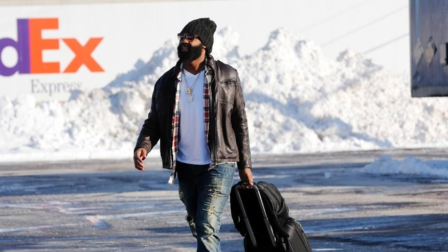 "Buffalo Bills player Brandon Spikes walks through a parking lot to the team charter flight for Detroit at the Buffalo Niagara International Airport, Friday, Nov. 21, 2014, in Cheektowaga, N.Y.  Snowed out in Buffalo, the Bills are heading to Detroit to play their ""home"" NFL football game against the New York Jets on Monday night, Nov. 24, 2014. (AP Photo/Mike Groll)"