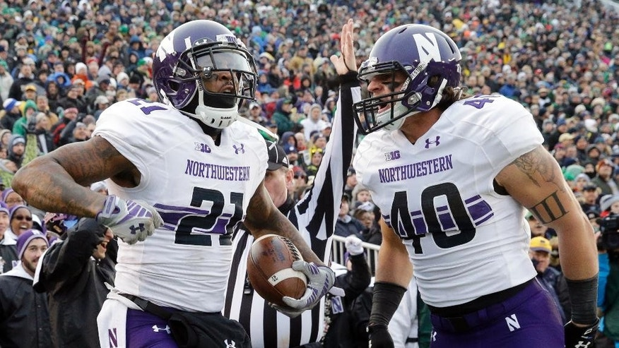 Northwestern wide receiver Kyle Prater (21) celebrates with super back Dan Vitale (40) after catching a touchdown pass during the first half of an NCAA college football game against Notre Dame in South Bend, Ind., Saturday, Nov. 15, 2014. (AP Photo/Nam Y. Huh)