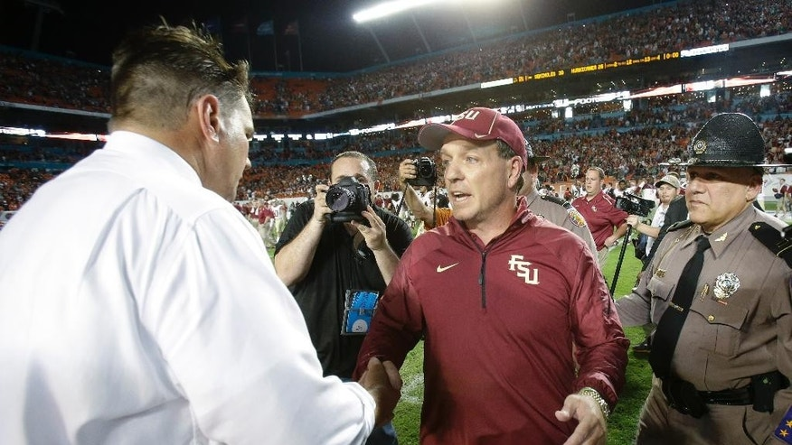 Florida State head coach Jimbo Fisher, center, and Miami head coach Al Golden congratulate each other after Florida State defeated Miami 30-26 in an NCAA College football game, Saturday, Nov. 15, 2014 in Miami Gardens, Fla. (AP Photo/Wilfredo Lee)