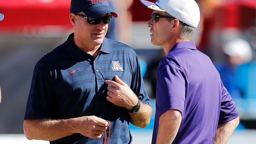Arizona head coach Rich Rodriguez, left, and Washington head coach Chris Petersen talk before an NCAA college football game, Saturday, Nov. 15, 2014, in Tucson, Ariz. (AP Photo/Rick Scuteri)