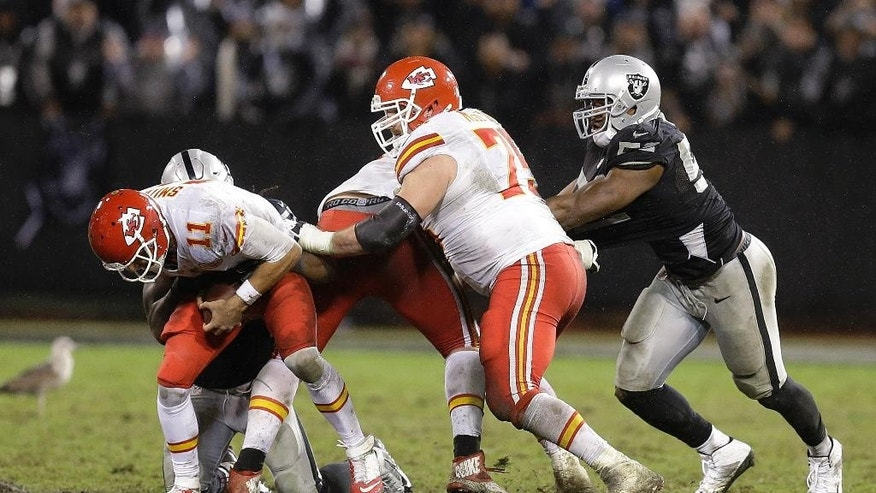 Kansas City Chiefs quarterback Alex Smith (11) is sacked by Oakland Raiders outside linebacker Sio Moore during the fourth quarter of an NFL football game in Oakland, Calif., Thursday, Nov. 20, 2014. The Raiders won 24-20. (AP Photo/Ben Margot)