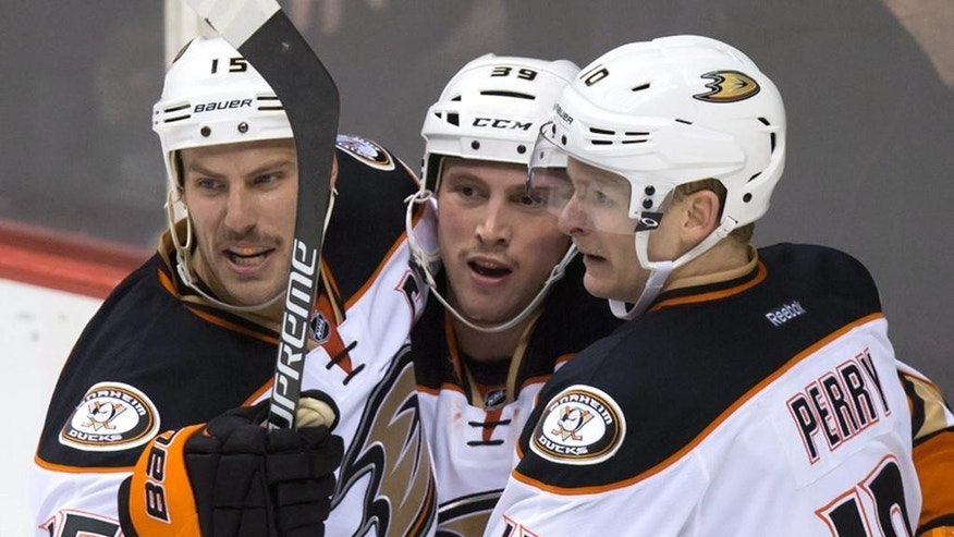 Anaheim Ducks' Ryan Getzlaf, Matt Beleskey and Corey Perry, from left celebrate Beleskey's tying goal against the Vancouver Canucks during the third period of an NHL hockey game Thursday, Nov. 20, 2014, in Vancouver, British Columbia. (AP Photo/The Canadian Press, Darryl Dyck)