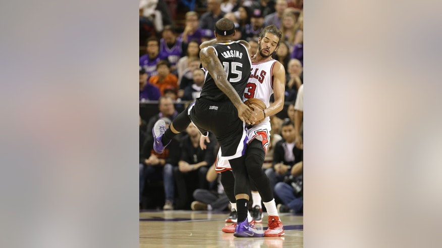 Sacramento Kings center DeMarcus Cousins, left, if fouled by Chicago Bulls center Joakim Noah, during the first quarter of an NBA basketball game in Sacramento, Calif., Thursday, Nov. 20, 2014. (AP Photo/Rich Pedroncelli)