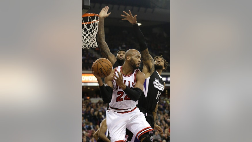 Chicago Bulls forward Taj Gibson, center, passes out of the double team of  Sacramento Kings' DeMarcus Cousins, left, and Derrick Williams during the first quarter of an NBA basketball game in Sacramento, Calif., Thursday, Nov. 20, 2014. (AP Photo/Rich Pedroncelli)