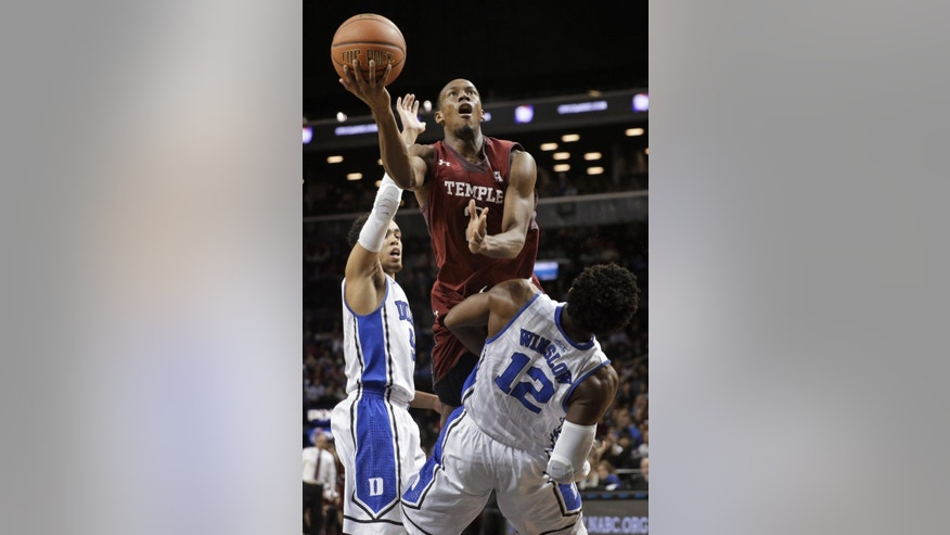 Temple's Will Cummings drives to the basket through Duke defenders, including Justice Winslow, during the first half of an NCAA college basketball game in New York, Friday, Nov. 21, 2014. (AP Photo/Seth Wenig)