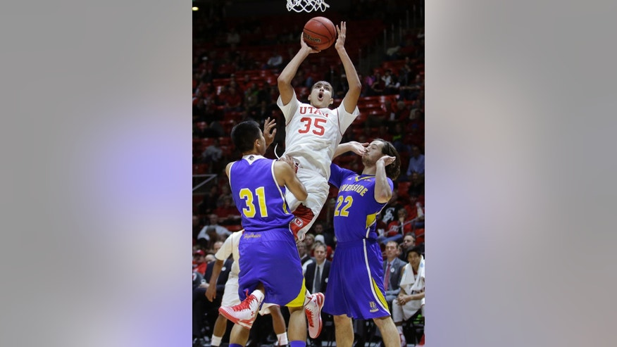 Utah's Kyle Kuzma (35) goes to the basket as UC Riverside's Chris Tang (31) and Colin Gruber (22) defend in the second half during an NCAA college basketball game Friday, Nov. 21, 2014, in Salt Lake City. Utah won 88-42. (AP Photo/Rick Bowmer)