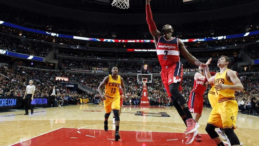 Washington Wizards guard John Wall (2) shoots in front of Cleveland Cavaliers guard Joe Harris (12) in the first half of an NBA basketball game, Friday, Nov. 21, 2014, in Washington. (AP Photo/Alex Brandon)