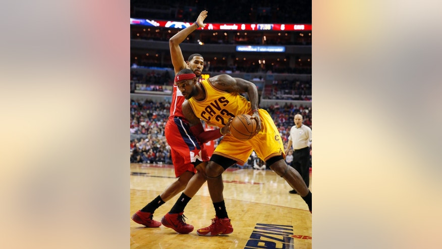 Cleveland Cavaliers forward LeBron James (23) leans into Washington Wizards guard Garrett Temple in the first half of an NBA basketball game, Friday, Nov. 21, 2014, in Washington. (AP Photo/Alex Brandon)