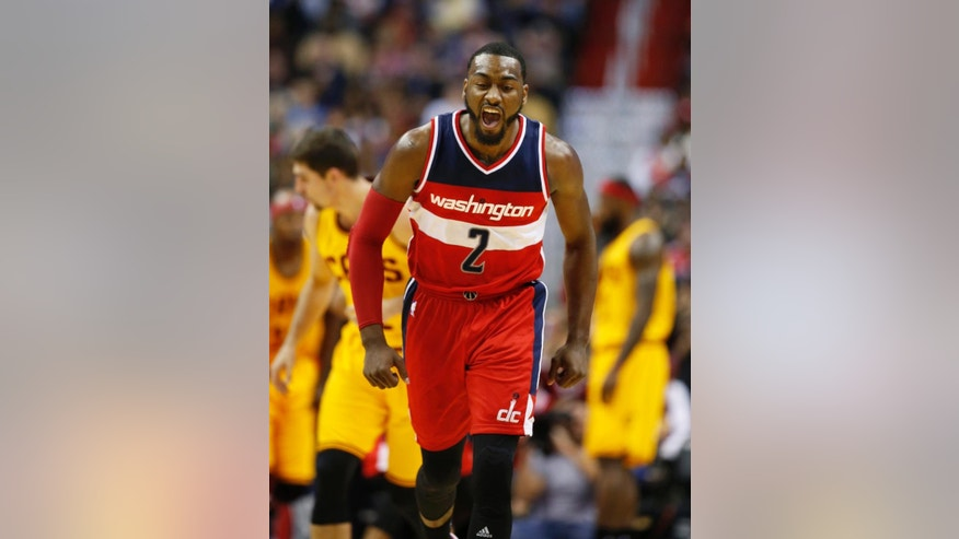 Washington Wizards guard John Wall reacts after a score in the first half of an NBA basketball game against the Cleveland Cavaliers, Friday, Nov. 21, 2014, in Washington. (AP Photo/Alex Brandon)