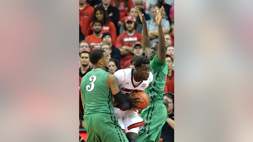 Louisville's Mangok Mathiang, center, attempts to fight his way through the defense of Marshall's Jay Johnson, left, and Cheikh Sane during the first half of an NCAA college basketball game Friday, Nov. 21, 2014, in Louisville, Ky. (AP Photo/Timothy D. Easley)