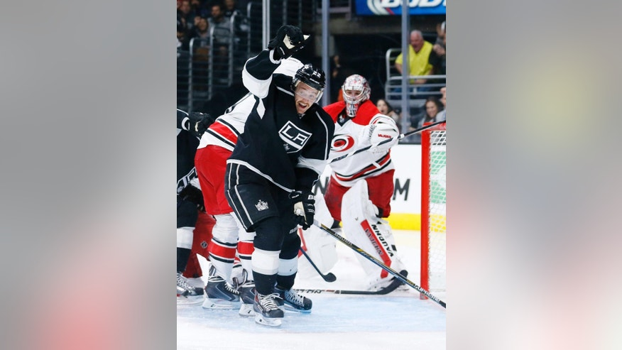 Los Angeles Kings center Trevor Lewis, left, celebrates scoring a goal past Carolina Hurricanes goalie Cam Ward, right, during the second period of an NHL hockey game, Thursday, Nov. 20, 2014, in Los Angeles. (AP Photo/Danny Moloshok)