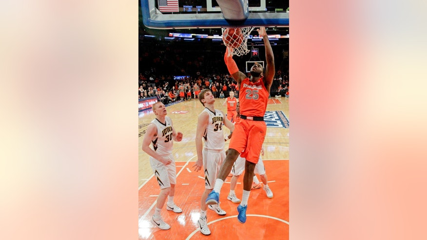 Syracuse's Rakeem Christmas (25) dunks the ball in front of Iowa's Aaron White (30) and Adam Woodbury (34) during the first half of an NCAA college basketball game at Madison Square Garden, Friday, Nov. 21, 2014, in New York. (AP Photo/Frank Franklin II)