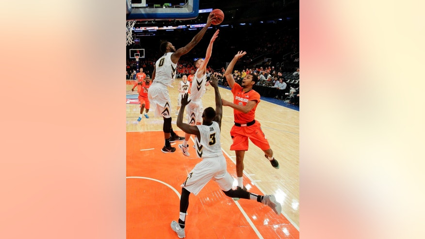 Iowa's Gabriel Olaseni, left, of Britain, blocks a shot by Syracuse's Michael Gbinije, right, during the first half of an NCAA college basketball game at Madison Square Garden, Friday, Nov. 21, 2014, in New York.  (AP Photo/Frank Franklin II)