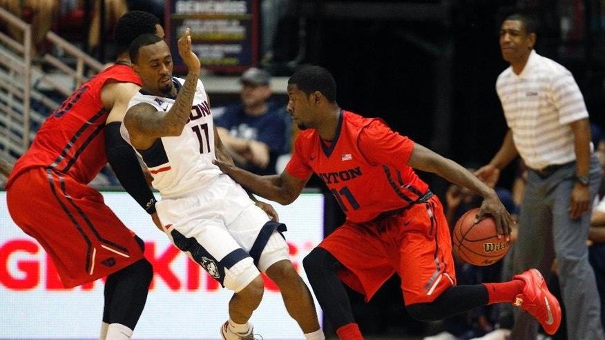 Dayton guard Scoochie Smith, right, dribbles past UConn guard Ryan Boatright during a NCAA college basketball game in San Juan, Puerto Rico, Friday, Nov. 21, 2014. (AP Photo/Ricardo Arduengo)