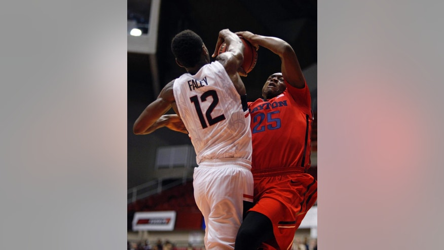 UConn forward Kentan Facey, left, blocks a shot from Dayton forward Kendall Pollard during a NCAA college basketball game in San Juan, Puerto Rico, Friday, Nov. 21, 2014. (AP Photo/Ricardo Arduengo)